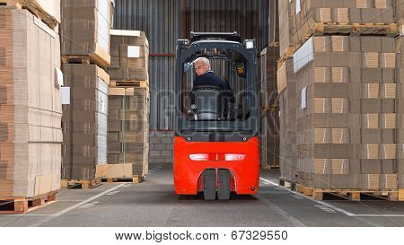 Expreinced forklift driver is driving his forklift backwards trough piled pallets with  cardboardboxes stack on it.