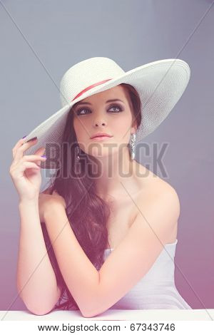Portrait of a beautiful young brunette woman. Wearing white hat over long loose curly hair. Open shoulders summer dress. Against grey pink vintage studio background.