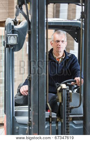 Forklift driver, manning the controls and steering wheel of his forklift in a large warehouse. Just in Time concept