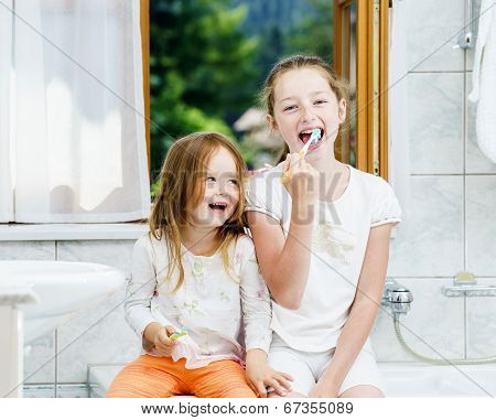 Two Sisters Cleaning The Teeth Together