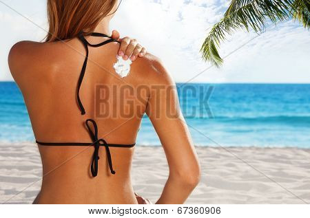Woman applying sun protection on tanned back