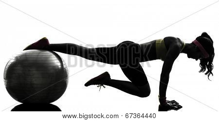 one woman exercising fitness workout plank position on fitness ball in silhouette on white background