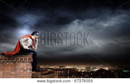 Thoughtful superman in cape and mask sitting on top of building