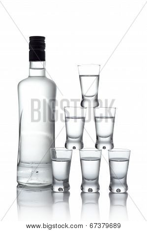 Bottle With Many Glasses Of Vodka Isolated On White Background