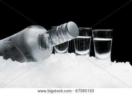Bottle Of Vodka With Glasses Standing On Ice On Black Background