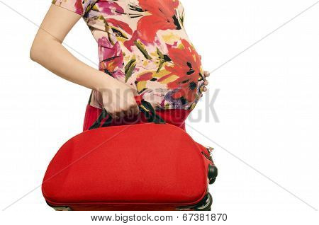 Woman expecting a baby holding a suitcase in her hands.