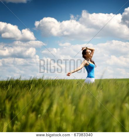 Happy carefree young woman in a green wheat field smiling as she trails her hand through the young plants, low angle distance view with copyspace against a beautiful blue sky with fluffy white clouds
