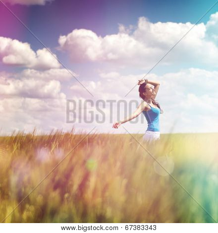 Woman frolicking in a summer field with colorful flare effect in rainbow or spectral colors under a cloudy blue sky, square format