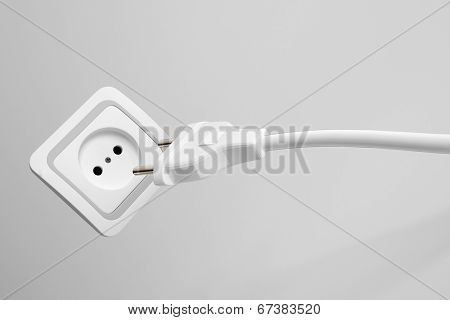 Two prong plug, cord and electrical power outlet providing a supply of domestic electricity on a grey wall, not plugged in
