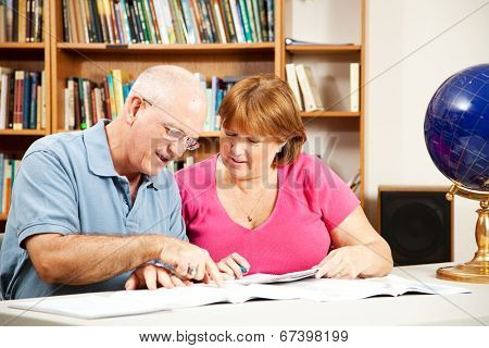 Middle-aged couple studying together in the library.