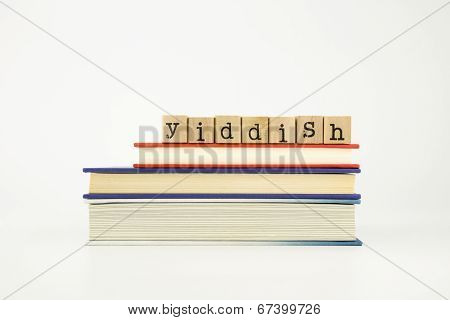 yiddish word on wood stamps stack on books foreign language and translation concept poster