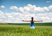 Image of a girl in a wheat field standing in the distance with her back to the camera and her arms outspread in celebration of a beautiful sunny summer day and freedom poster