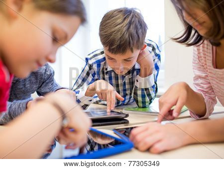 education, elementary school, learning, technology and people concept - group of school kids with tablet pc computer having fun on break in classroom poster