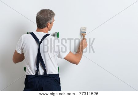 Painter On Stepladder Painting Wall With Brush
