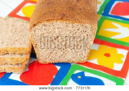 A fresh home made bread on the colorful breadboard poster