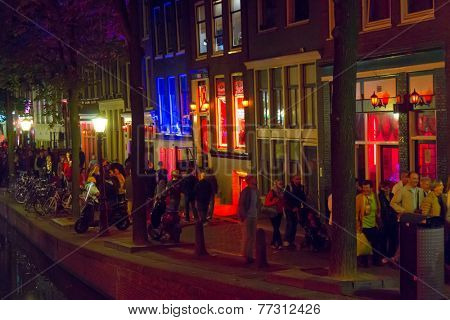 AMSTERDAM, NETHERLANDS - AUGUST 31: Tourists visit Red Light District at night on August 31, 2014 in Amsterdam, Netherlands. In this area there are prostitutes, sex shops and live sex shows