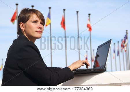 business woman working on a background of international flags