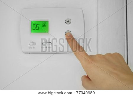 A woman adjusting a wall thermostat temperature poster