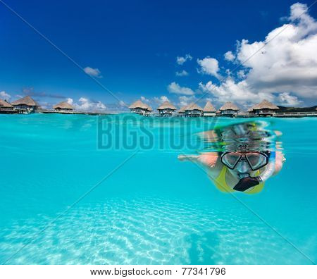 Underwater photo of woman snorkeling in clear tropical waters in front of overwater villas poster