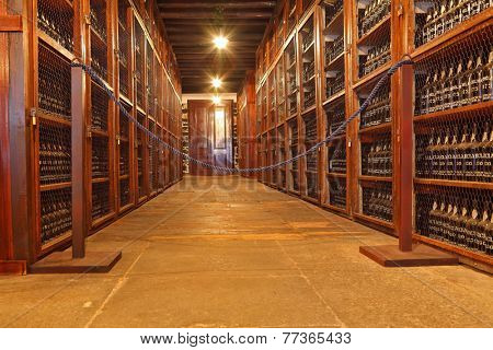 FUNCHAL, MADEIRA - OCTOBER 08, 2011: Museum - repository of expensive vintage wine Madera. Long rows of shelves made of mahogany. The shelves are made with sweet wine bottles Madera
