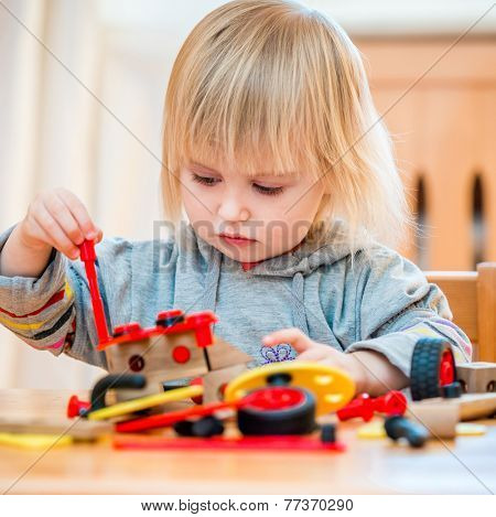 cute two-year old baby girl at home in the nursery playing with constructor