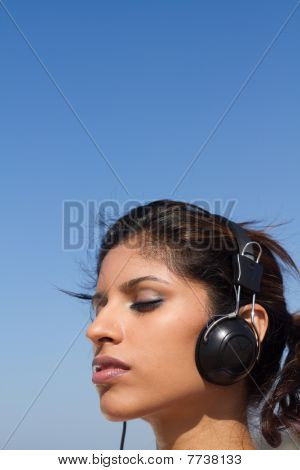 close-up of pretty woman listening to music