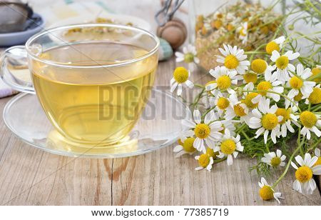 Cup of herbal chamomile tea on a wooden table. Chamomile tea in a transparent cup and camomile flowers on wooden table. Herbal tea for baby's stomach. Copyspace. poster