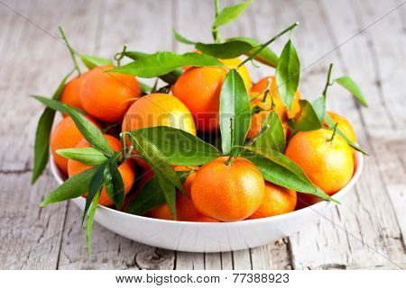 fresh tangerines in a bowl on rustic wooden background
