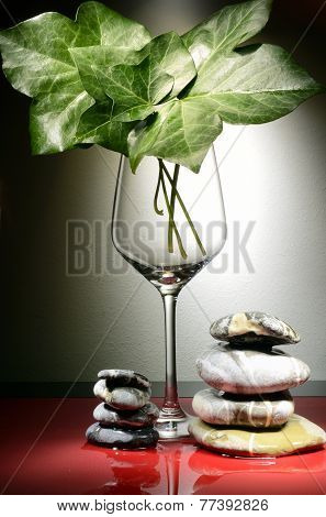 Glass With Ivy Leaves And Pebbles