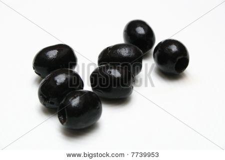 seven fresh black olives lying on white bakground