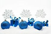 Decoration of blue christmas gifts and baubles and snowflakes on snow on white background poster