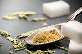 spoon with stevia rebaudiana bertoni powder and dried leaves vs sugar poster