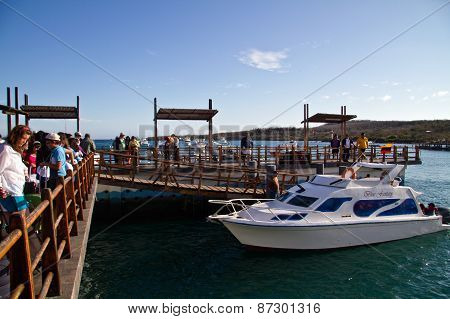 Unidentified tourists in the port of San Cristobal island, Galapagos