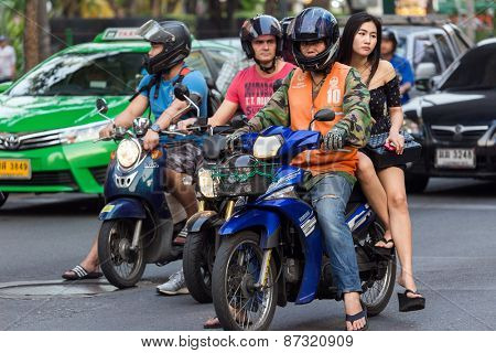 BANGKOK, THAILAND, February 15, 2015: A moto taxi is carrying a young Thai lady on his motorbike in the Sukhumvit road near the Thong Lor BTS station in Bangkok, Thailand