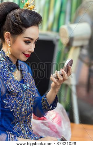 BANGKOK, THAILAND, February 17, 2015: A Thai lady dancer is checking her makeup make up on a mirror before the show at the Krung Kasem floating market in the Thewet district of Bangkok, Thailand