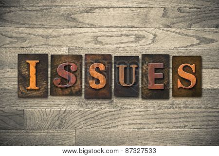 "The word ""ISSUES"" theme written in vintage ink stained wooden letterpress type on a wood grained background. poster"