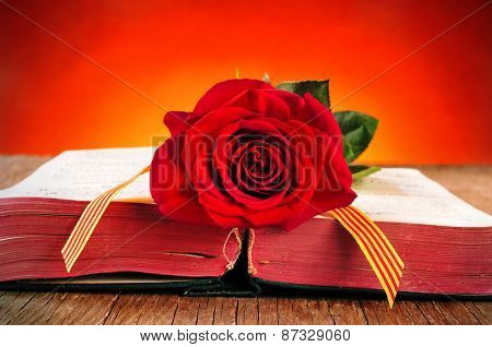 a red rose and the catalan flag on an old book for Sant Jordi, the Saint Georges Day, when it is tradition to give red roses and books in Catalonia, Spain poster