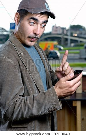 Funny portrait of a man with mobile phone outdoors