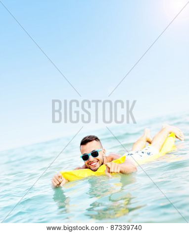 A picture of a young man swimming on a matress in the Baltic Sea