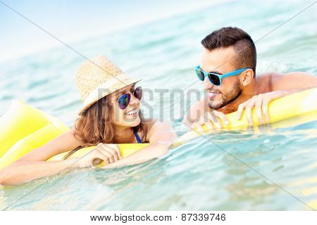 A picture of a young couple having fun on a matress in the sea
