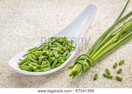 a spoon of chopped fresh chives with a bunch against withe painted barn wood
