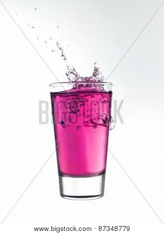 Splash in a glass of pink lemonade isolated on white background