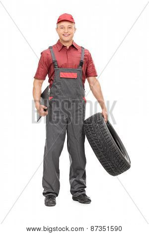 Full length portrait of a joyful mechanic in a gray jumpsuit, holding a tire in one hand and a clipboard in the other isolated on white background