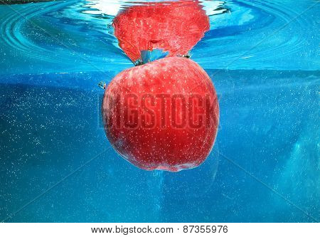 apple in water on a blue background poster