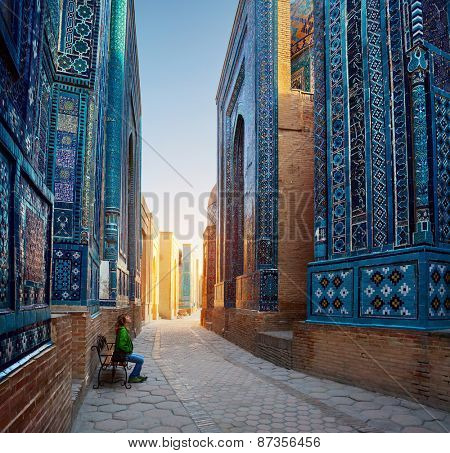 Woman relaxing on the bench and enjoying beauty of the ancient complex of Shah-i-Zinda, Samarkand, Uzbekistan poster