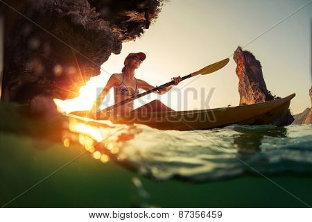 Young lady paddling the kayak in a bay with limestone mountains. Split shot with underwater view at sunset