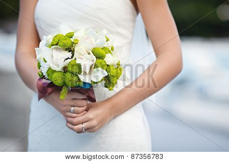 beautiful wedding bouquet of filin green and Cymbidium flowers in hands of the bride