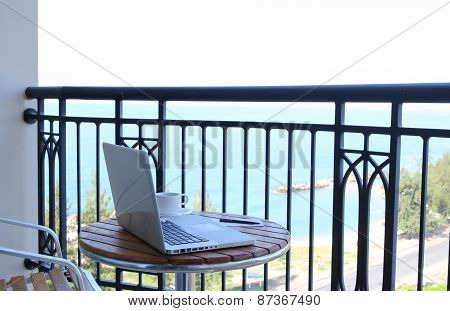 Computer Laptop On Balcony And Coffee