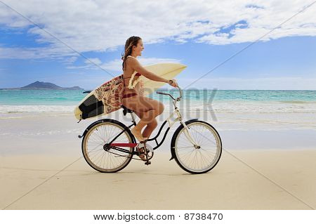 girl with surfboard and bike