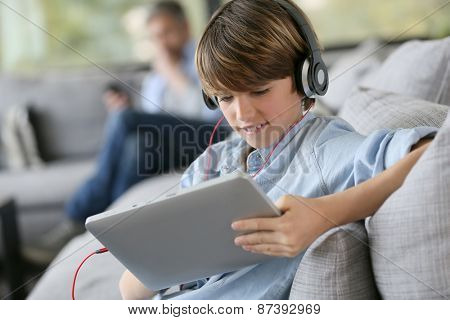 Tenager watching movie on tablet with headphones on
